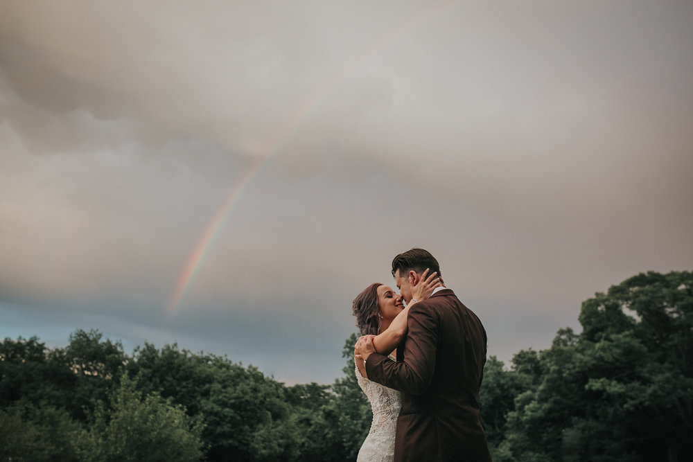 froom-bride-holding-each-other-in-front-of-rainbow-desmoines-iowa-art-center-raelyn-ramey-photography.jpg