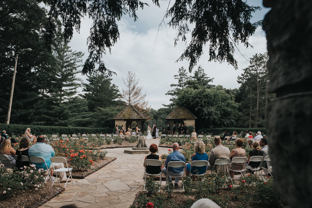full-wedding-party-and-guests-during-ceremony-desmoines-iowa-rose-garden-raelyn-ramey-photography.jpg