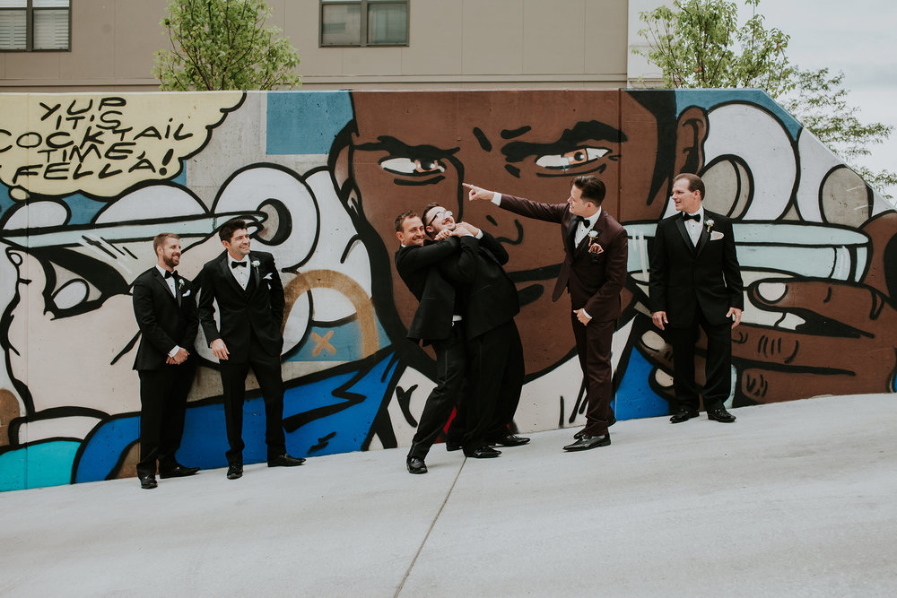groom-and-groomsmen-in-front-of-mural-desmoines-iowa-ac-hotel-raelyn-ramey-photography.jpg