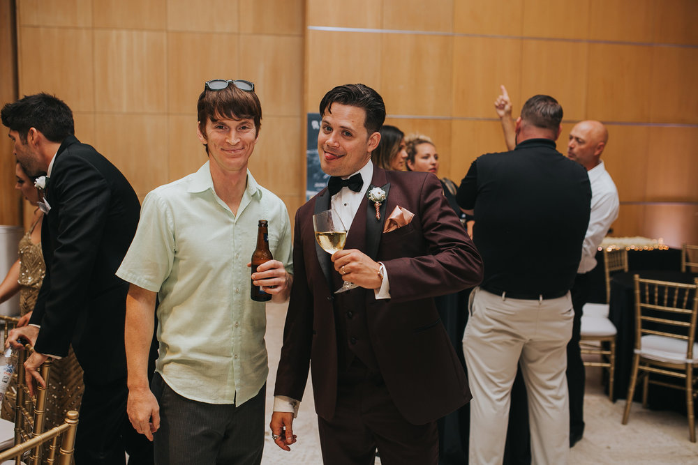 groom-posing-with-tongue-out-with-a-guest-desmoines-iowa-art-center-raelyn-ramey-photography.jpg