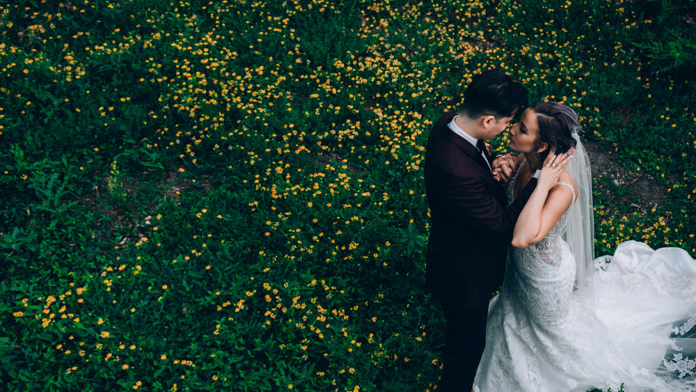 wedding-couple-holding-each-other-going-to-kiss-standing-in-grass-desmoines-iowa-art-center-raelyn-ramey-photography.jpg