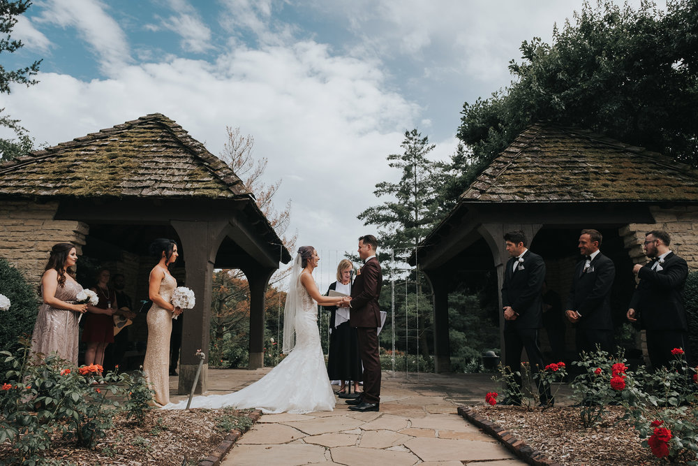 wedding-couple-holding-hands-during-ceremony-desmoines-iowa-rose-garden-raelyn-ramey-photography.jpg