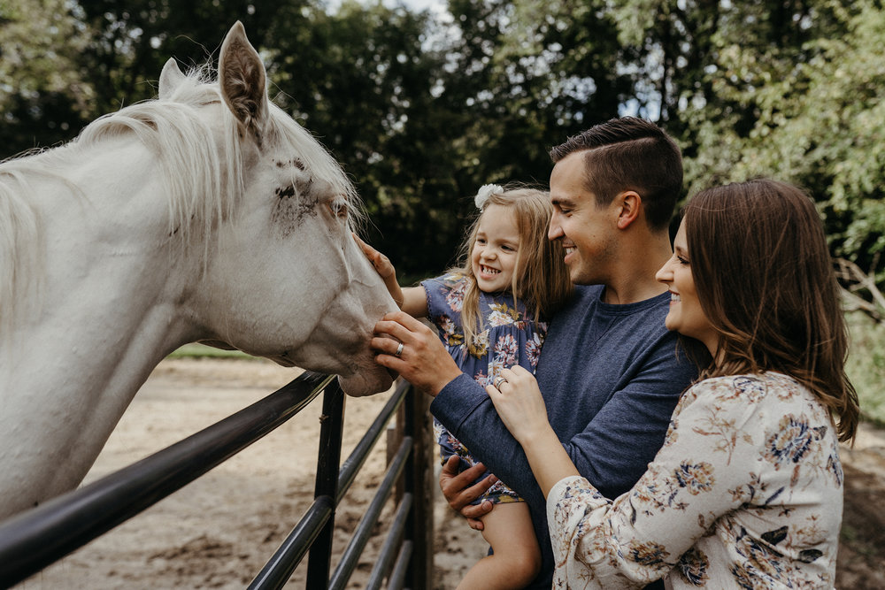 mueller-family-parents-holding-daughter-petting-white-horse-granger-iowa-raelyn-ramey-photography.jpg