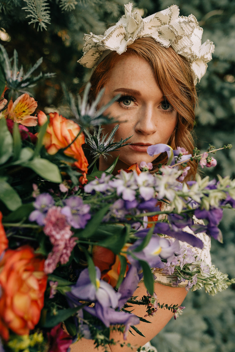 bride-holding-bouquet-close-to-eyes-myrtle-mae-iris-aisle-dame-maiden-lavender-blue-floral-raelyn-ramey-photography.jpg