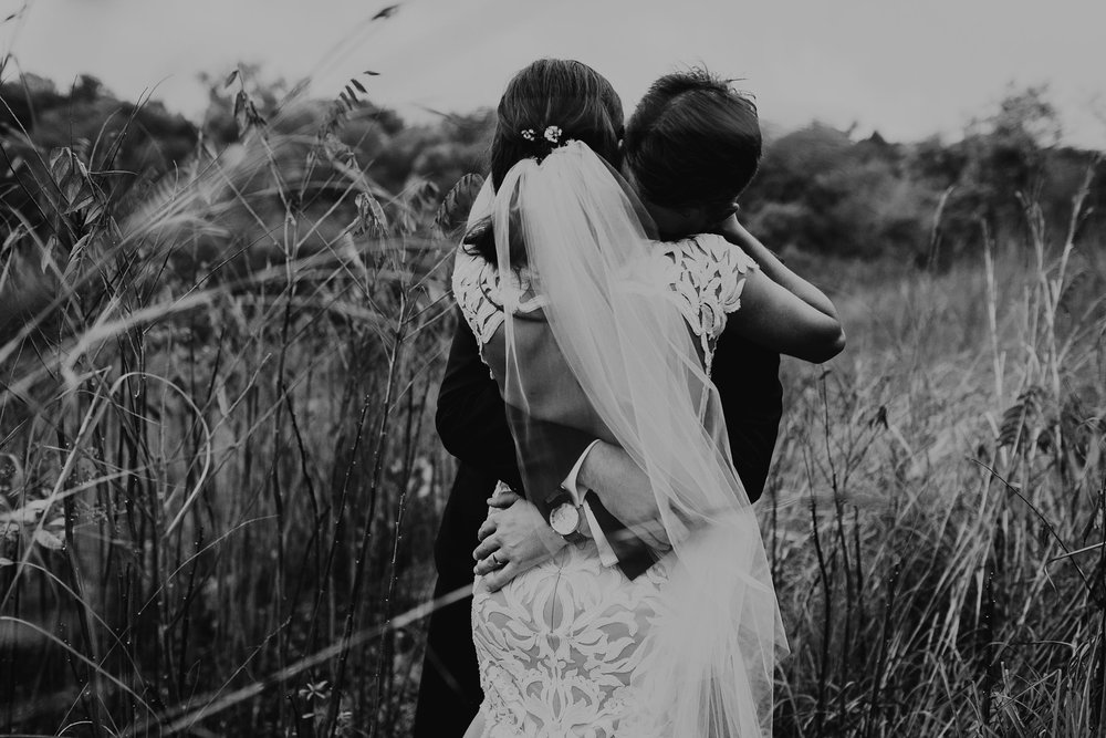 bride-and-groom-hugging-at-a-park-omaha-nebraska-raelyn-ramey-photography.jpg