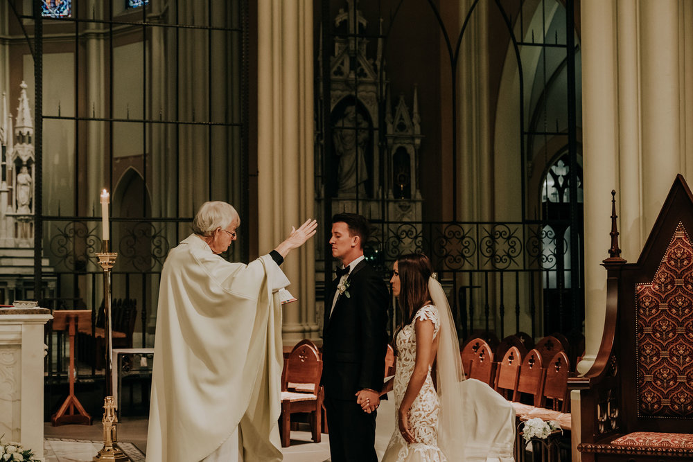 bride-groom-being-blessed-at-ceremony-st-johns-church-at-creighton-omaha-nebraska-raelyn-ramey-photography.jpg