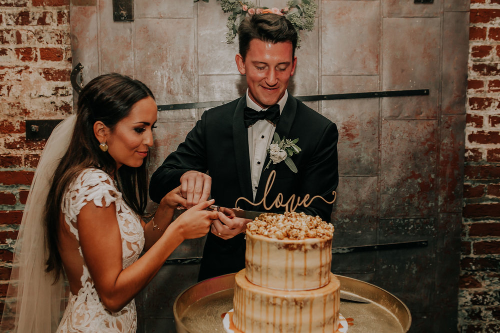 bride-groom-cutting-carmel-popcorn-cake-founders-one-nine-omaha-nebraska-raelyn-ramey-photography.jpg