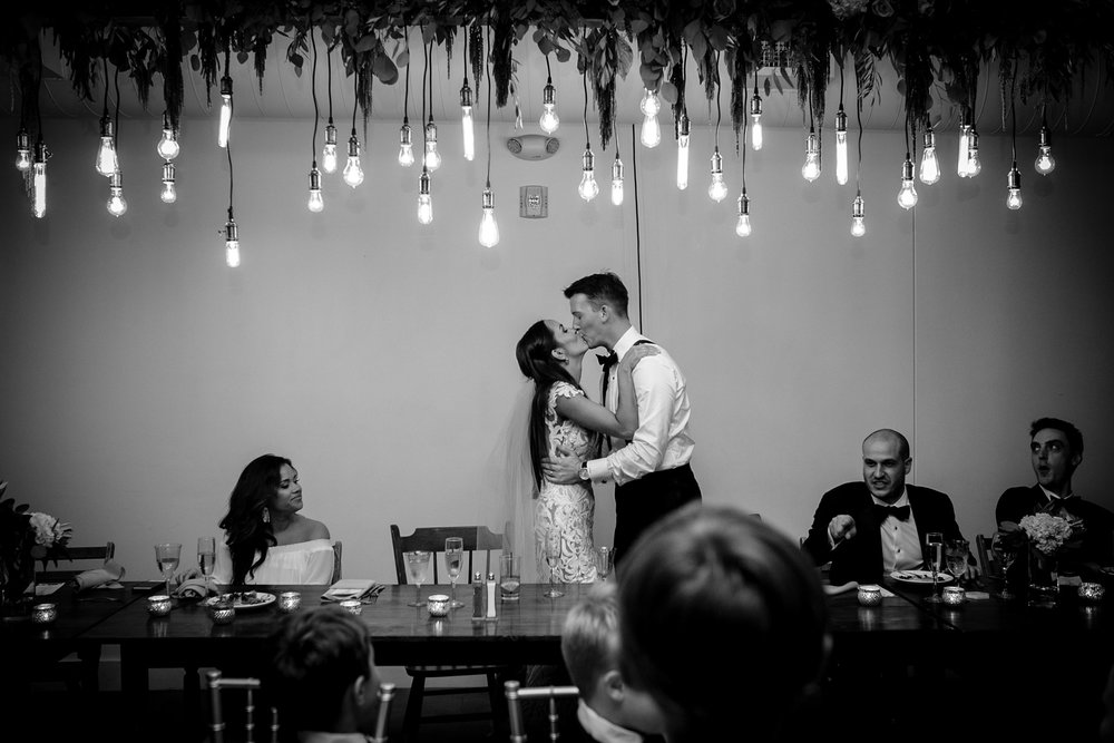 bride-groom-kissing-at-head-table-founders-one-nine-omaha-nebraska-raelyn-ramey-photography.jpg
