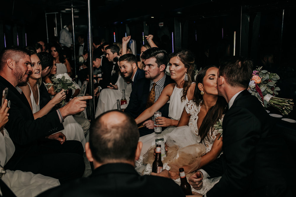 bride-groom-kissing-on-party-bus-omaha-nebraska-raelyn-ramey-photography.jpg