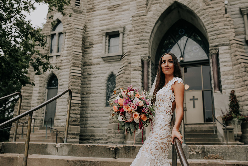 bride-posing-in-front-of-st-johns-church-at-creighton-omaha-nebraska-raelyn-ramey-photography.jpg