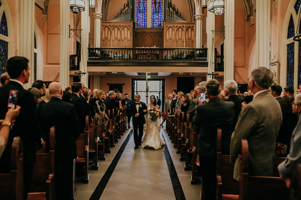 bride-walking-down-aisle-with-father-st-johns-church-at-creighton-omaha-nebraska-raelyn-ramey-photography.jpg