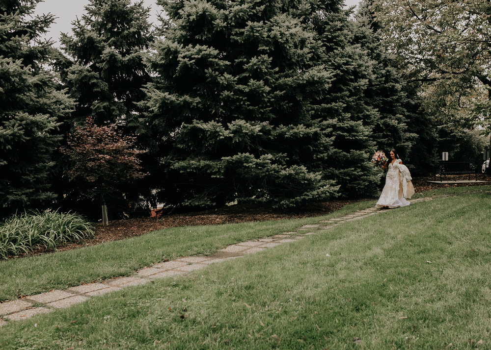 bride-walking-to-groom-for-first-look-st-johns-church-at-creighton-omaha-nebraska-raelyn-ramey-photography.jpg