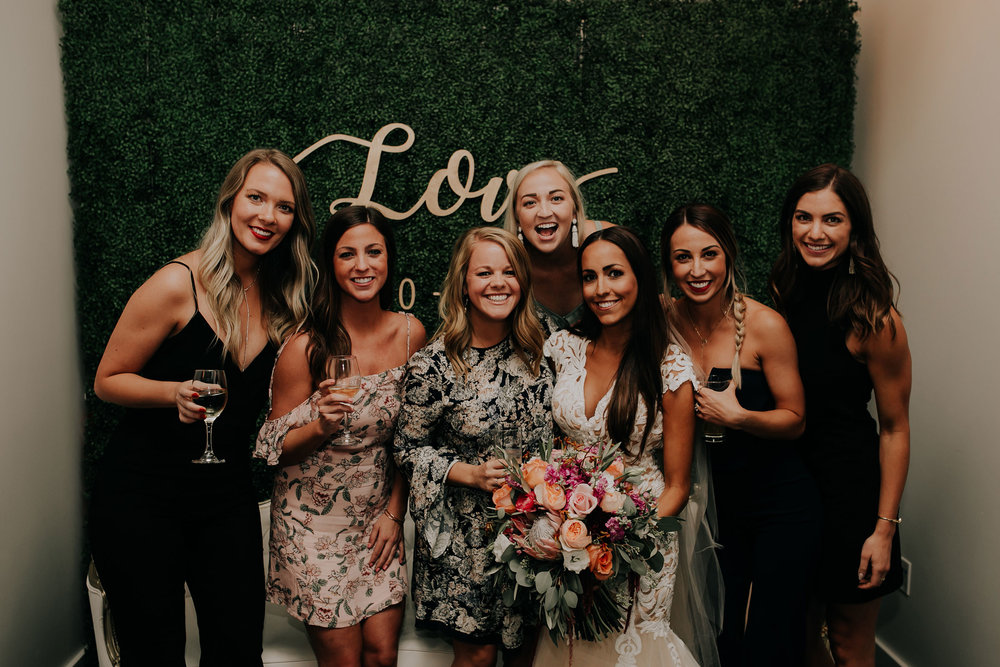 bride-with-friends-in-front-of-photo-booth-founders-one-nine-omaha-nebraska-raelyn-ramey-photography.jpg