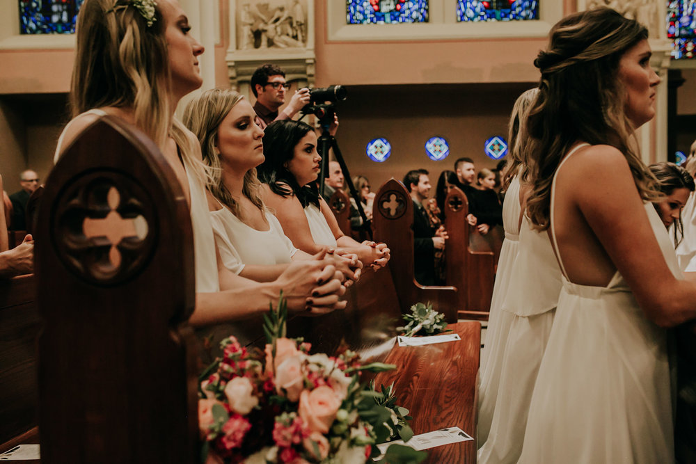 bridesmaids-praying-during-ceremony-st-johns-church-at-creighton-omaha-nebraska-raelyn-ramey-photography.jpg
