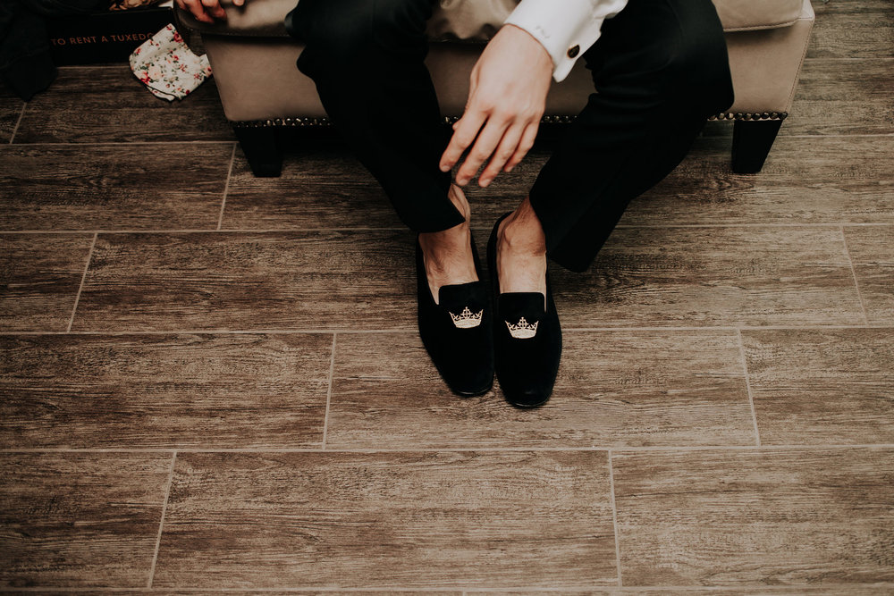 groom-getting-shoes-on-hilton-omaha-nebraska-raelyn-ramey-photography.jpg