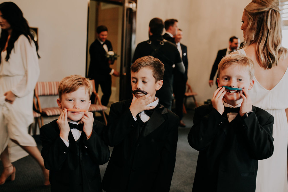 kids-playing-with-twizzlers-before-ceremony-st-johns-church-at-creighton-omaha-nebraska-raelyn-ramey-photography.jpg