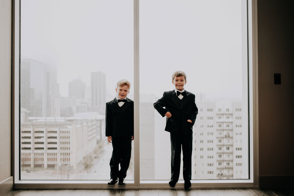 ring-bearers-standing-in-window-hilton-omaha-nebraska-raelyn-ramey-photography.jpg