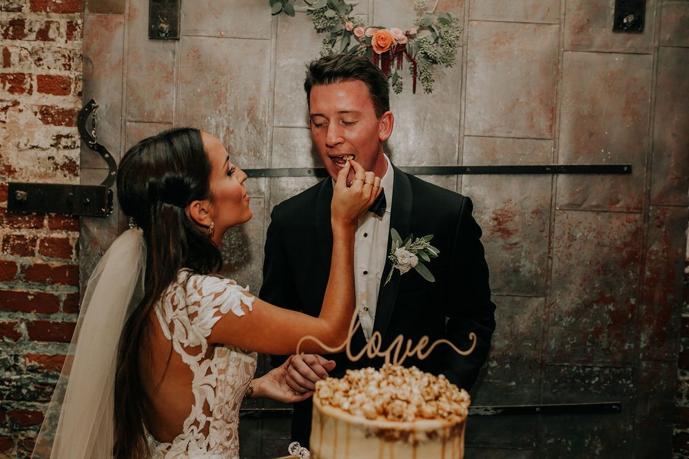 wedding-couple-eating-popcorn-cake-founders-one-nine-omaha-nebraska-raelyn-ramey-photography.jpg