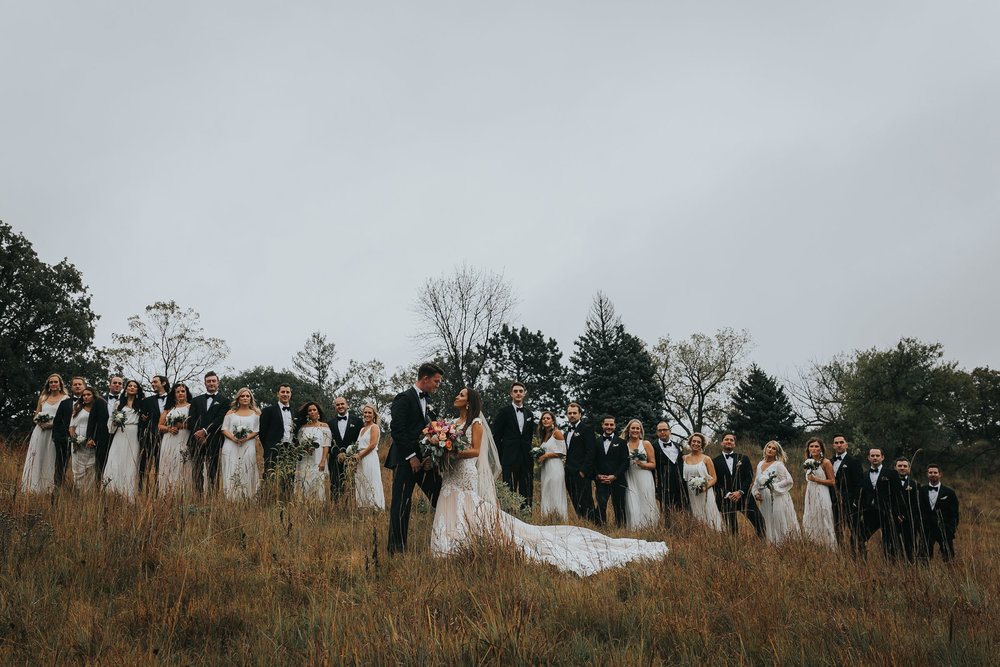 wedding-party-of-twelve-standing-on-hill-top-omaha-nebraska-raelyn-ramey-photography.jpg