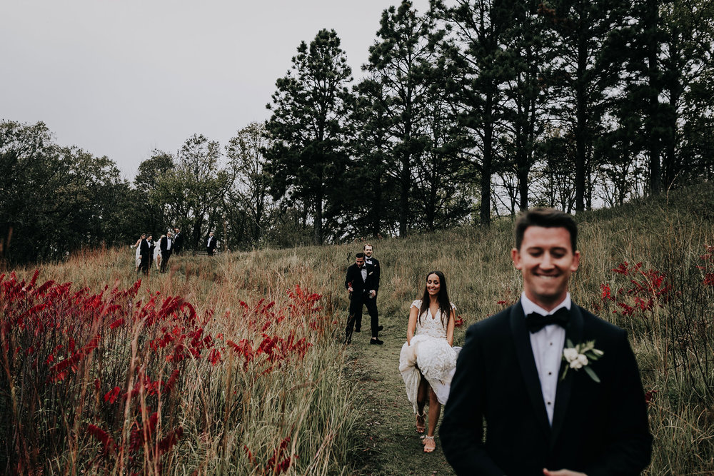 wedding-party-walking-down-hill-omaha-nebraska-raelyn-ramey-photography.jpg
