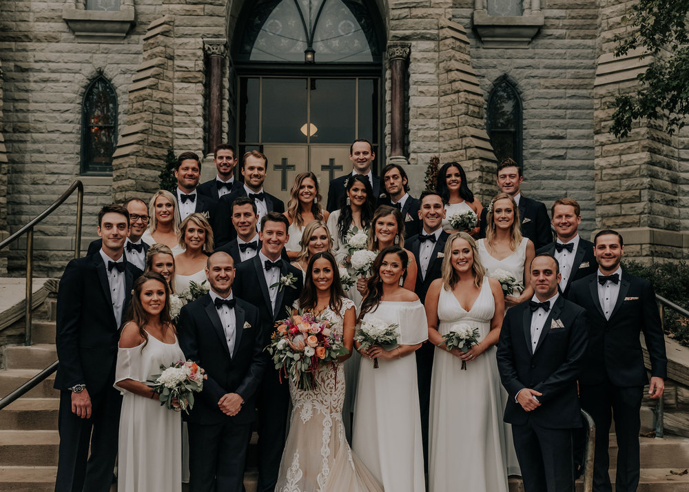 whole-wedding-party-posing-on-stairs-st-johns-church-at-creighton-omaha-nebraska-raelyn-ramey-photography.jpg
