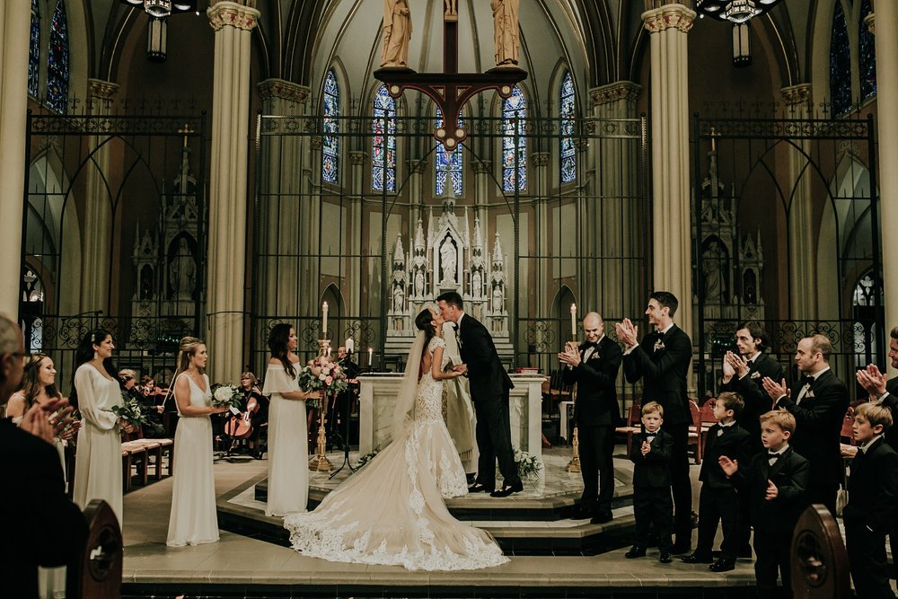 bride-groom-kiss-at-ceremony-st-johns-church-at-creighton-omaha-nebraska-raelyn-ramey-photography.jpg