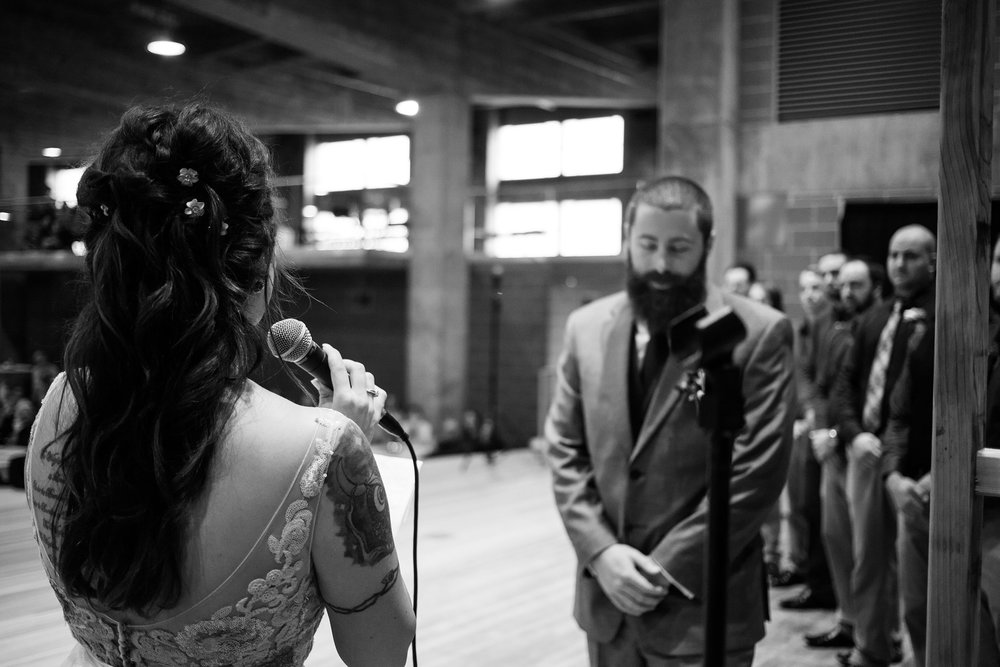 bride-from-behind-reading-vows-to-groom-pella-plaza-desmoines-iowa-raelyn-ramey-photography.jpg