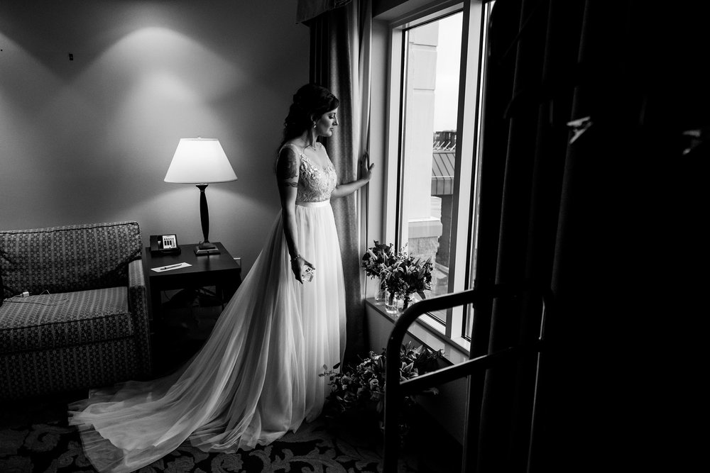 bride-looking-out-window-prairie-meadows-desmoines-iowa-raelyn-ramey-photography.jpg
