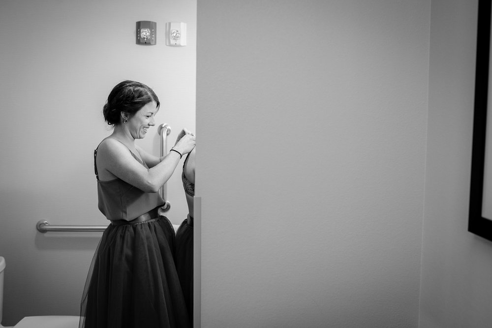 bridesmaid-helping-get-ready-prairie-meadows-desmoines-iowa-raelyn-ramey-photography.jpg