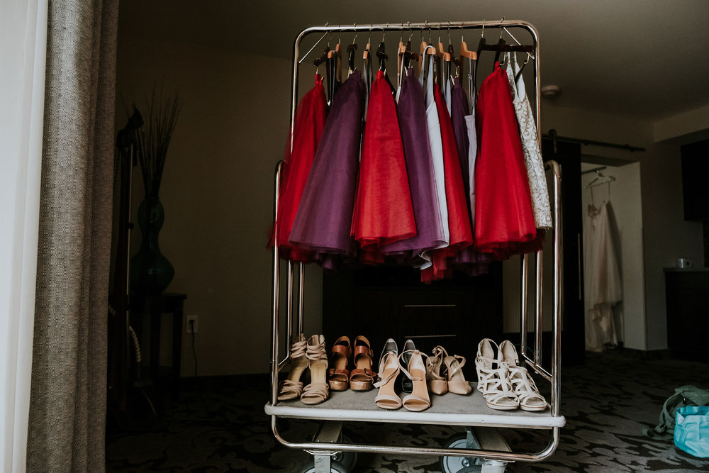 bridesmaids-dresses-and-shoes-hanging-up-prairie-meadows-desmoines-iowa-raelyn-ramey-photography.jpg