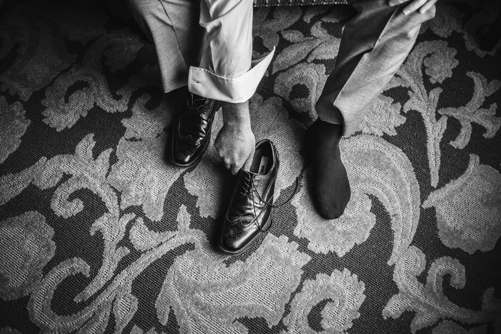 groom-putting-shoes-on-prairie-meadows-desmoines-iowa-raelyn-ramey-photography.jpg