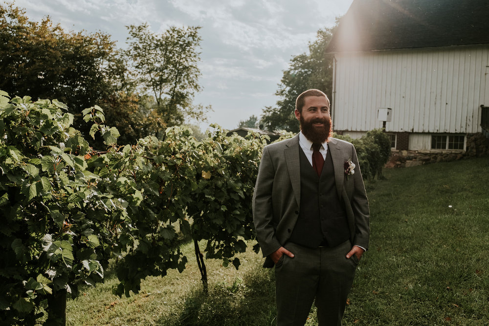 groom-standing-next-to-grape-vines-iowa-state-fairgrounds-desmoines-iowa-raelyn-ramey-photography.jpg