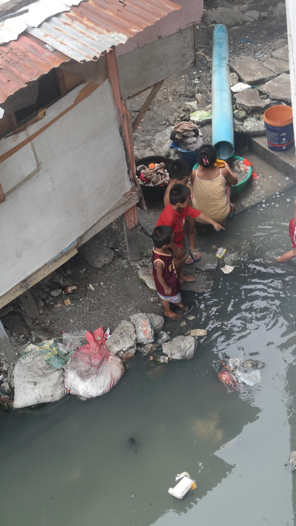 Yllä olevat kuvat ovat samasta joesta ja tässä kuvassa perheen äiti pesee vaatteitaan ja lapset leikkivät tässä joessa. Perheen koti on kuvassa näkyvä.
