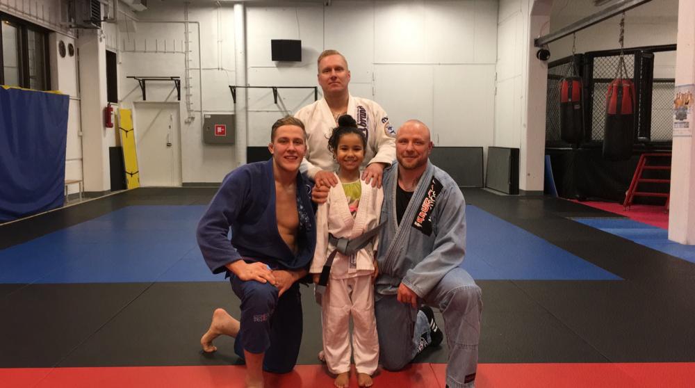 Alyna iloisena uusi vyö lanteilla, valmentajien Jesse Vuorion, Tomi Tervasen ja Miika Mehmetin kanssa.