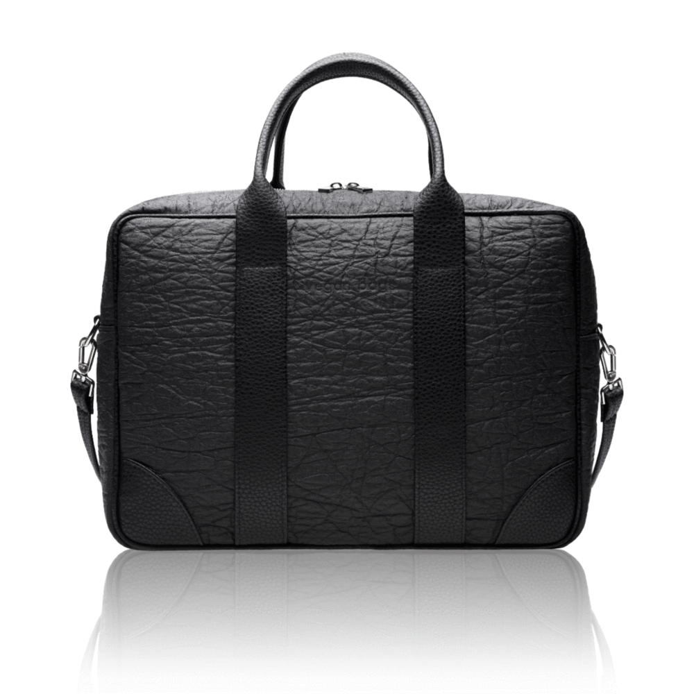 "Investing in the right bag is crucial when travelling for business or presenting in the boardroom and this Alexandra K. briefcase is an astute choice. It has been handcrafted in Poland from black pebble grain vegan leather and contrasting Pineapple leather, a true conversation starter. It has an internal padded slip for your laptop and and organizational pockets for essentials, it's ideal for ladies & gents on the go. Fits up to a 15"" laptop."