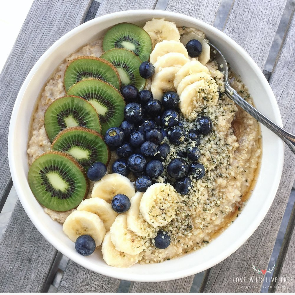 Quick + Easy Vegan Oatmeal topped with fresh kiwi, blueberries, bananas, pure maple syrup and Manitoba Harvest hemp hearts.