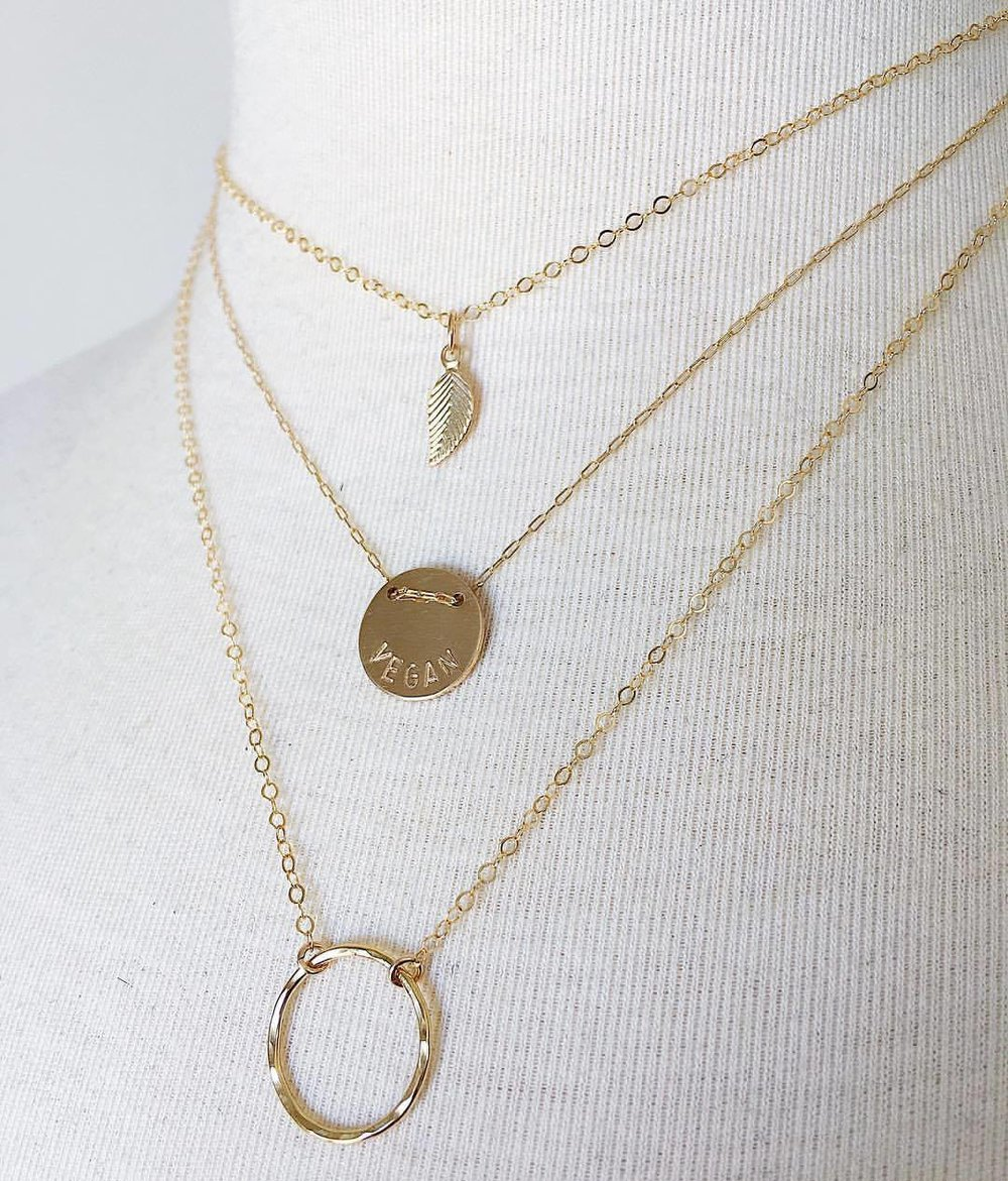 Compassion Layers in gold  featuring the  Earth Saver  necklace with gold fill components + the  'VEGAN' Button Necklace in Gold + Gold Drop Circle Necklace by Jewels by SJB.