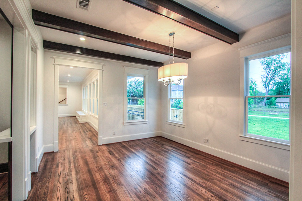 Large dining area also has an unobstructed view of the nature trail with stained ceiling beams, art wall between the windows, and a designer fixture. Lighting here and elsewhere dimmable to 5%.