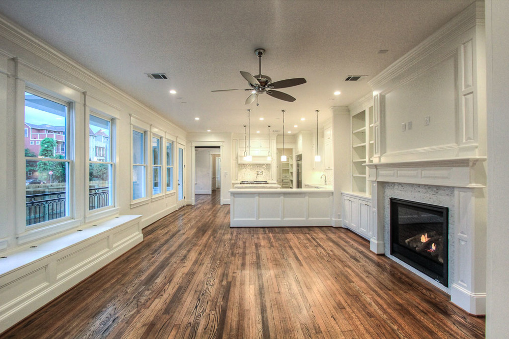 Spacious great room adjacent to kitchen has an wide open view of the greenbelt featuring the builder's signature site-built shelving and storage, including a built-in bench. Carrara tile surrounds the fireplace and reclaimed wood flooring throughout.