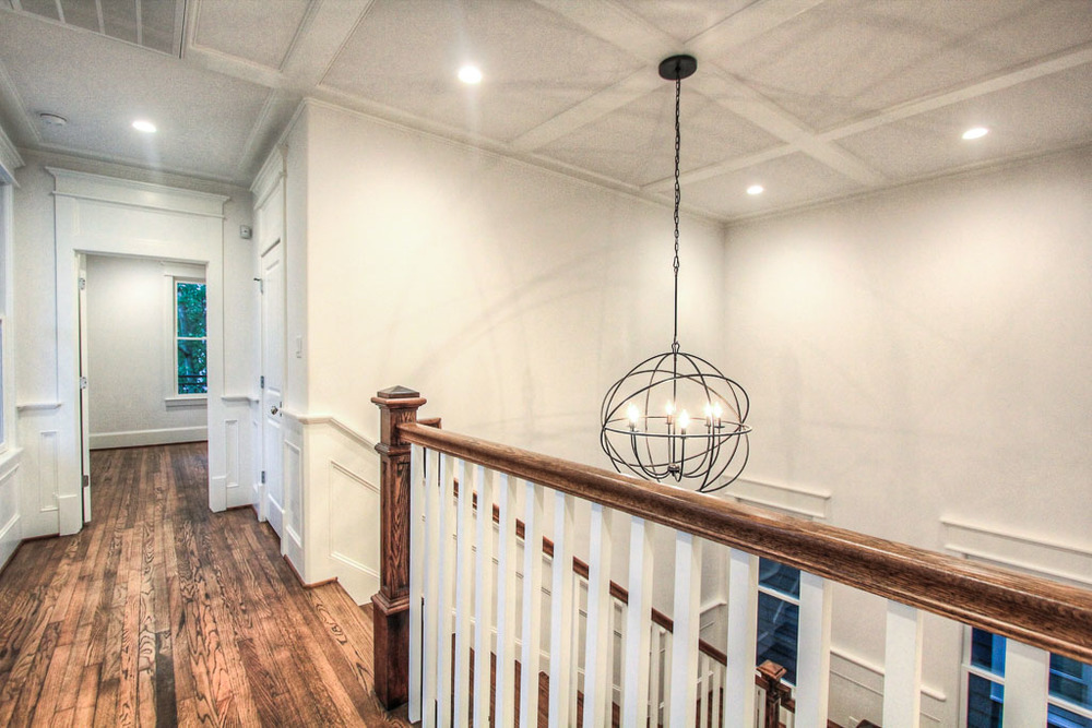 Beautiful paneled ceiling above the wide, open staircase and an elegant lighting fixture bring you to the expansive mezzanine, where a hallway leads to the master retreat.