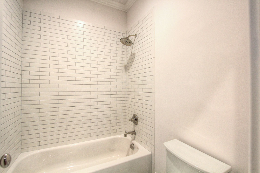 This secondary bathroom has beautiful glass tile in the tub.