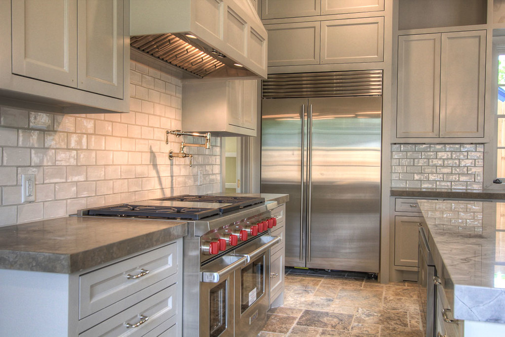 "Walker Zanger tile backsplash, 48"" Wolf chef's range with double oven and convenient potfiller. 48"" Sub Zero refrigerator. Lagos Azul limestone countertops continue the mix of natural textures."