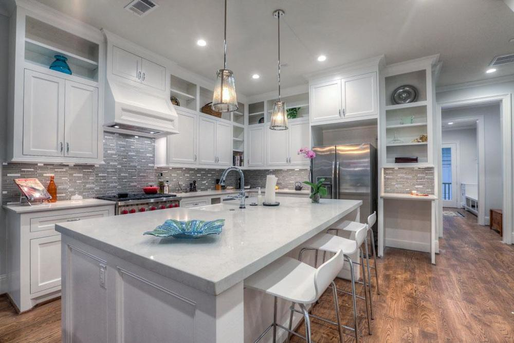 Kitchen features large island with seating, custom cabinetry, and a mosaic tile backsplash.