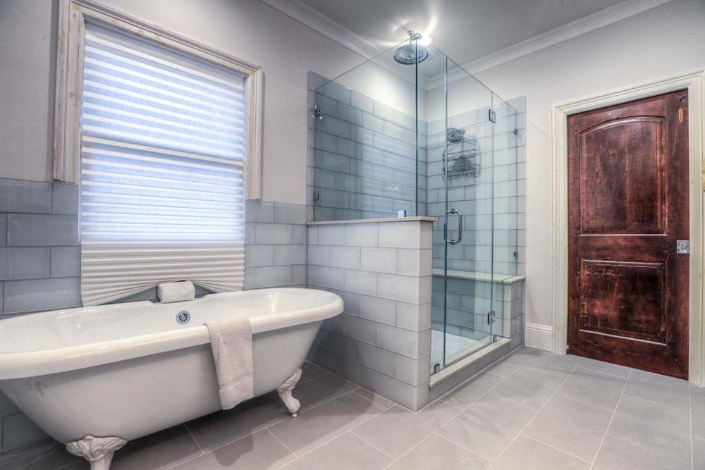 Master bathroom with freestanding tub, and hue shower with glass tile walls.