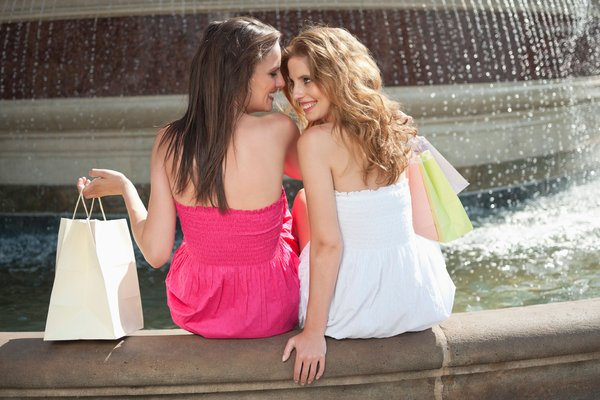 Back view of two young female friends communicating while sitting by water fountain