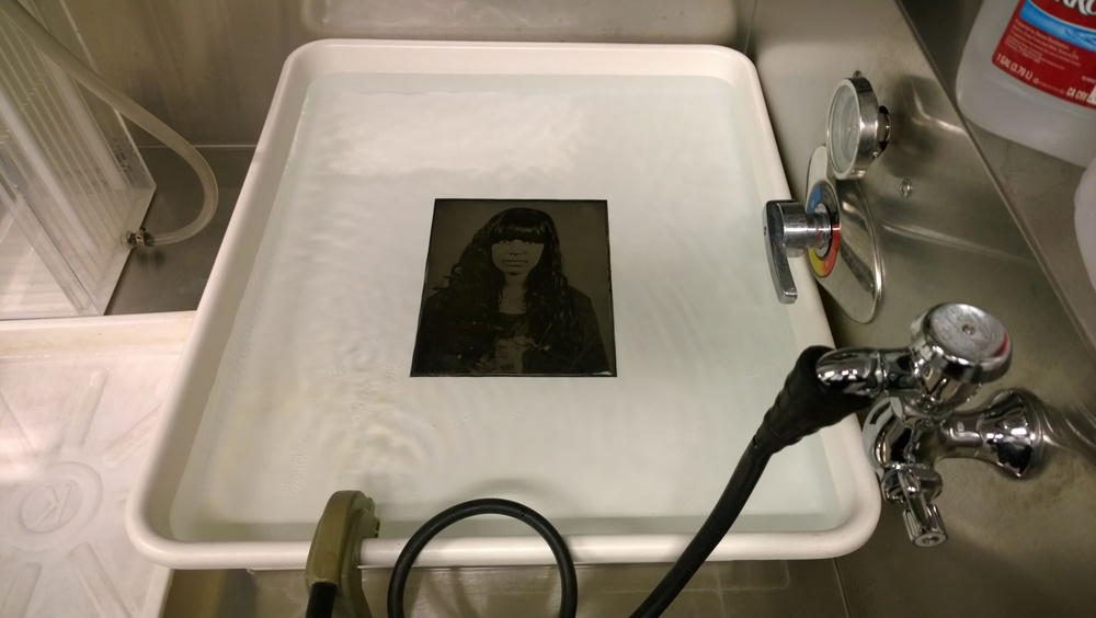 A tintype sits in the wash after developing.