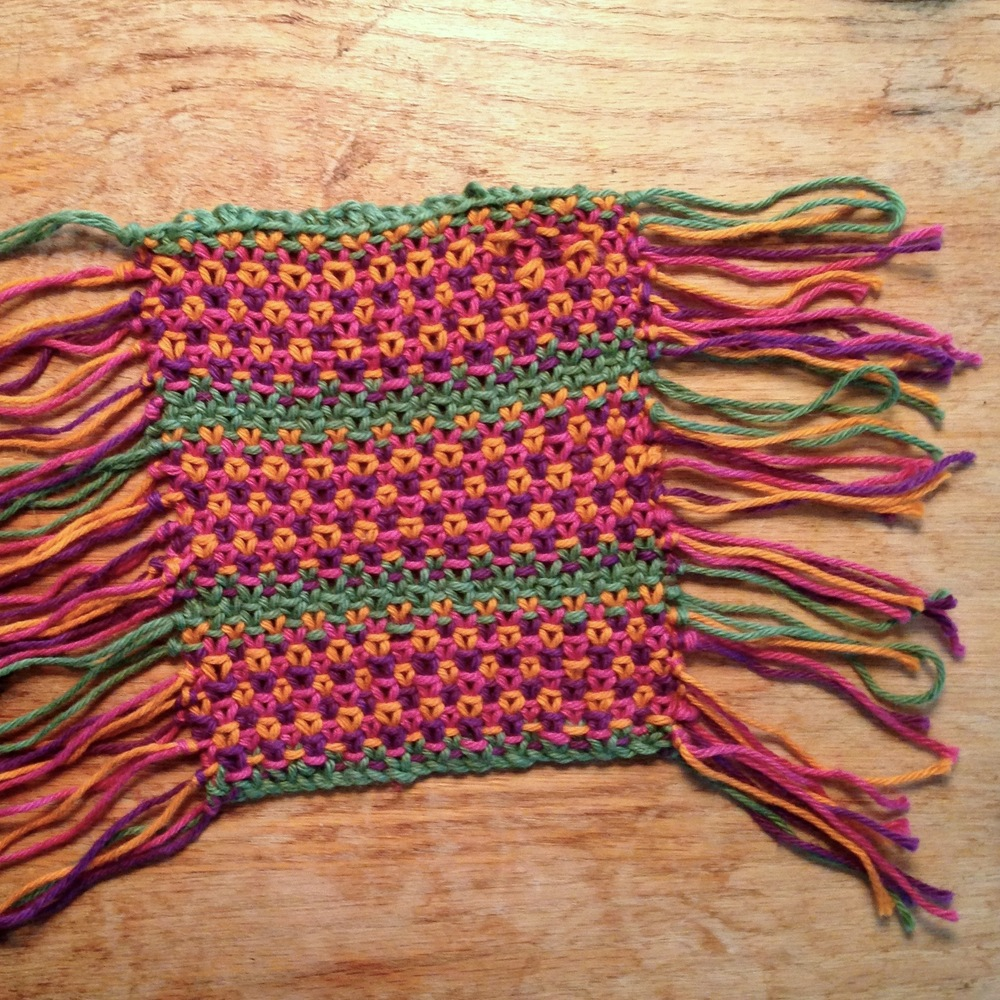 Completed coaster showing the knotted tails at the end/beginning of every row, before...