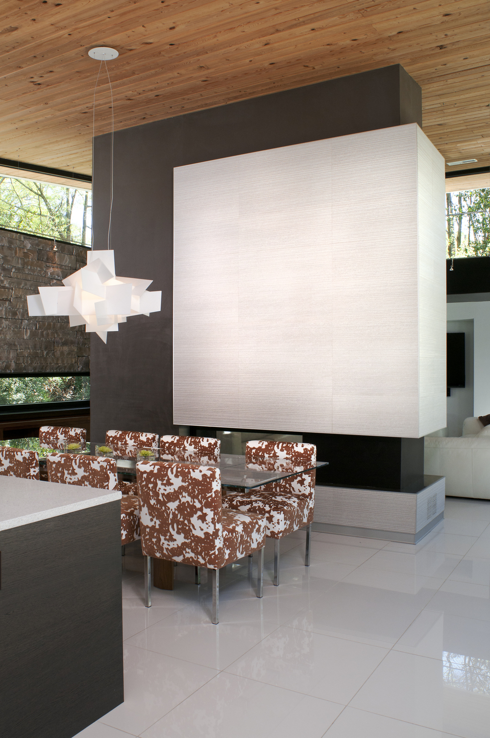 Creating a focal point through color blocking, Porcelanosa tile was selected in a grooved texture to compliment the linear orientation of the stone and the hard surfaces were softened by the suede wall covering from Innovations to add a contrasting energy and make the fireplace wall appear to float.  The Big Bang light fixture was also highlighted against the dark suede where it was previously lost in the white sheetrock.