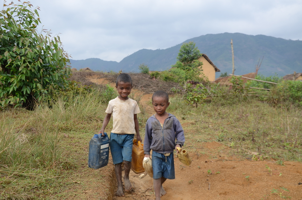 Françoise's child,  Loni, five, with his classmate, Mbina, four years old, on their way to fetch water before going to school. Morarano village, Miakadaza fokontany, Sabotsy Anjiro commune, Moramanga region, Madagascar. November 2014.