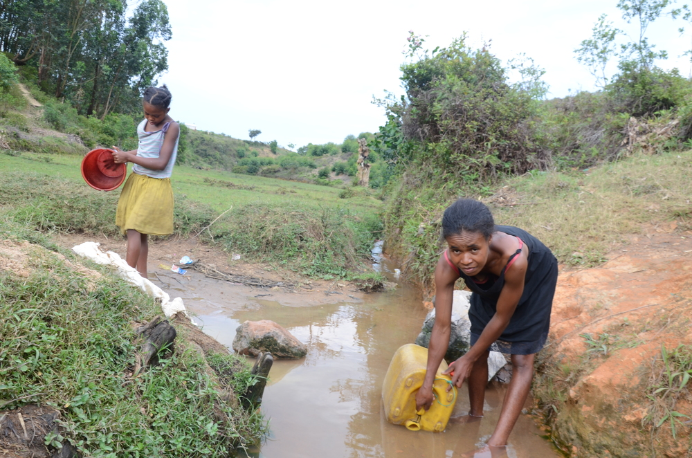 """We don't have any choice. We have to use and drink this dirty water every single day."" Françoise fetching water at their drinking water source. Morarano village, Miakadaza fokontany, Sabotsy Anjiro commune, Moramanga region, Madagascar. November 2014."